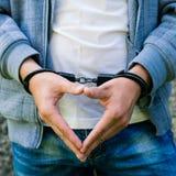 Jonge misdadige status in handcuffs, in openlucht Concept misdaad stock foto's