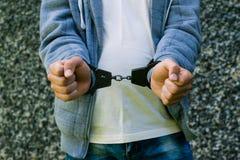 Jonge misdadige status in handcuffs, in openlucht Concept misdaad stock fotografie
