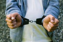 Jonge misdadige status in handcuffs, in openlucht Concept misdaad royalty-vrije stock afbeelding