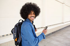 Jonge moderne mens die met zak en celtelefoon glimlachen Royalty-vrije Stock Foto