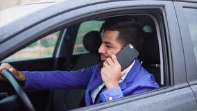 Jonge moderne moslimzakenman die op smartphone in de auto spreken stock videobeelden