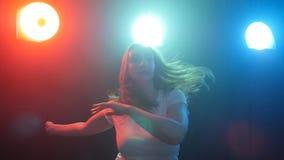 Jonge moderne stijldanser op een donkere achtergrond met rook en lichten stock video