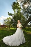 Jonge modieuze bruid, mooi blonde modelmeisje met modieus huwelijkskapsel, in witte kantkleding met boeket van royalty-vrije stock foto's