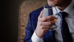 Jonge modieuze kerel die een glas whisky houden Sluit omhoog cinematic stock video