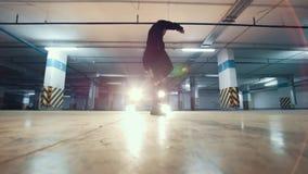 Jonge modieuze kerel die freerunner een tik van de muur in de garage doen, parkour acrobatische elementen, langzame motie stock footage