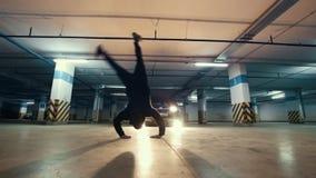 Jonge modieuze kerel die freerunner een tik van de muur in de garage doen, parkour acrobatische elementen, langzame motie stock video