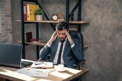Jonge modieuze knappe zakenman die bij zijn bureau in het bureau werken hij heeft een vreselijke hoofdpijn royalty-vrije stock afbeeldingen