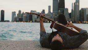 Jonge modieuze mens die op de kust van het meer van Michigan in Chicago, Amerika en het spelen van de akoestische gitaar liggen stock videobeelden