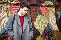 Jonge modieuze mens die zich voor kleurrijke muur bevinden Stock Foto