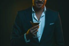 Jonge modieuze mens in het glas van de smokingholding met cocktail royalty-vrije stock afbeelding