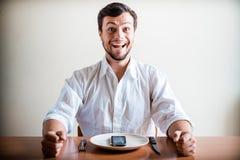 Jonge modieuze mens met wit overhemd en telefoon op de schotel Royalty-vrije Stock Afbeelding