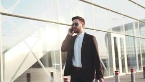 Jonge modieuze mens in zonnebril die op zijn telefoon spreken, en koffer trekken terwijl het weggaan van de luchthaven Het succes stock videobeelden