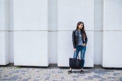 Jonge modieuze vrouw die met handtas op de stadsstraat lopen Royalty-vrije Stock Afbeelding
