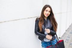 Jonge modieuze vrouw die met handtas op de stadsstraat lopen Royalty-vrije Stock Fotografie