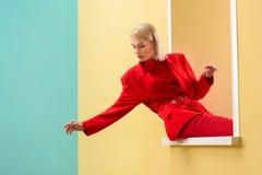 jonge modieuze vrouw die in rood kostuum uit kijken stock foto's