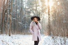 Jonge modieuze vrouw in een hoed en een laag die zich in de winter bevinden fores stock foto's