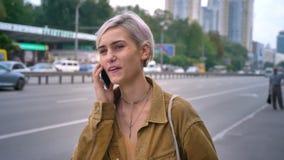 Jonge modieuze vrouw met roze haar die op taxi of bus wachten en op telefoon, stedelijke straatachtergrond spreken stock videobeelden