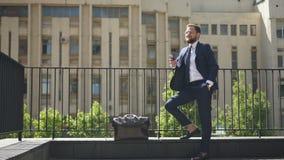 Jonge modieuze zakenman die met smartphone zich op steen de bouwachtergrond bevinden in stad stock footage