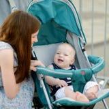 Jonge moeder die aan haar baby in een wandelwagen spreken Royalty-vrije Stock Fotografie