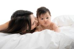Jonge moeder die in bed met haar liggen weinig babyjongen royalty-vrije stock fotografie