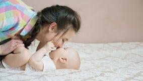 Jonge moeder die in bed met haar pasgeboren babyjongen liggen stock footage