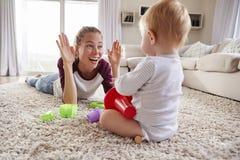 Jonge moeder die bij vloer het spelen met peuterzoon thuis liggen stock afbeelding