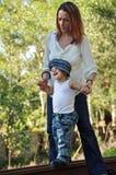 Jonge moeder die de jongen van de peuterbaby helpen te lopen Stock Afbeelding