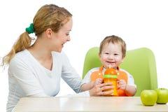 Jonge moeder die drank helpt haar babyjongen Stock Foto