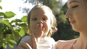 Jonge moeder die een babymeisje op handen houden terwijl baby die kersen rechtstreeks van de boom eten stock video