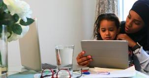 Jonge moeder die een digitale tablet met haar dochter op lijst 4k gebruiken stock video