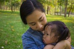 Jonge moeder die en het schreeuwen koesteren kalmeren weinig dochter, Aziatische moeder die haar schreeuwend kind proberen te tro stock foto