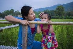 Jonge moeder die en het schreeuwen koesteren kalmeren weinig dochter, Aziatische moeder die haar schreeuwend kind proberen te tro royalty-vrije stock foto