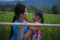 Jonge moeder die en het schreeuwen koesteren kalmeren weinig dochter, Aziatische moeder die haar schreeuwend kind proberen te tro stock fotografie