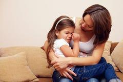 Jonge moeder die en schreeuwend babymeisje kalmeert koestert Stock Fotografie
