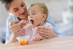 Jonge moeder die fruitsalade geven aan haar babymeisje royalty-vrije stock afbeeldingen