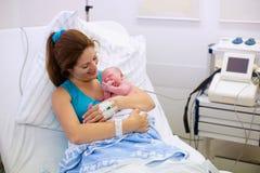 Jonge moeder die geboorte geven aan een baby stock foto