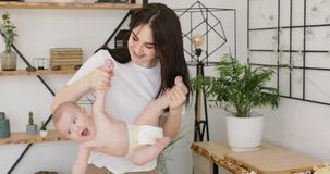 Jonge moeder die haar babybovenkant houden - neer stock videobeelden