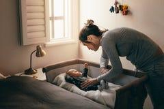 Jonge moeder die haar babyslaap bekijken in een voederbak stock afbeeldingen