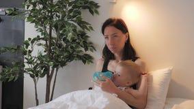 Jonge moeder die haar babyzoon met een fles melk thuis voeden stock video