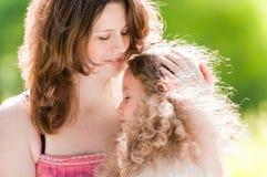 Jonge moeder die haar dochter koestert Stock Afbeeldingen