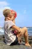 Jonge moeder die haar dochter op strand koesteren Stock Fotografie