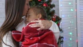 Jonge moeder die haar houden die weinig dochter in handen slapen dichtbij Kerstboom stock footage