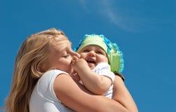 Jonge moeder die haar kind kust Stock Afbeelding