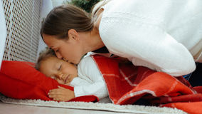 Jonge moeder die haar kussen die weinig dochter slapen Royalty-vrije Stock Foto's