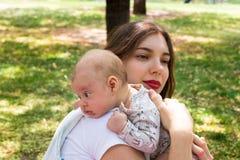 Jonge moeder die haar leuke baby op de schouder buiten in het park tijdens aardige zonnige dag geven, Zuigelingshoofd die op de s royalty-vrije stock afbeelding