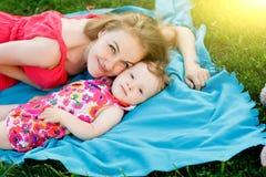 Jonge moeder die haar meisje koesteren die op blauwe deken liggen Royalty-vrije Stock Foto's