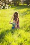 Jonge moeder die haar mooie kleine baby helpen om eerste stappen te maken stock fotografie