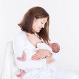 Jonge moeder die haar pasgeboren baby de borst geven Royalty-vrije Stock Foto's
