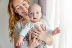 Jonge moeder die haar pasgeboren kind houden Stock Afbeelding