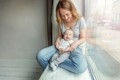 Jonge moeder die haar pasgeboren kind houden stock foto